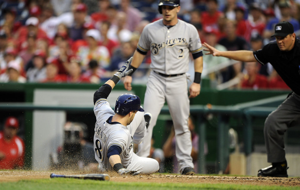 Photo - Milwaukee Brewers' Ryan Braun (8) slides home to score as he and Scooter Gennett (2) both scored on a single by Aramis Ramirez during the third inning of a baseball game against the Washington Nationals, Friday, July 18, 2014, in Washington. (AP Photo/Nick Wass)