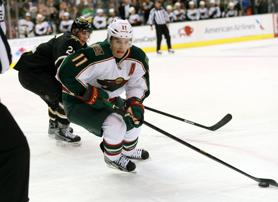 Photo - Minnesota Wild left wing Zach Parise (11) makes his move down the boards as Dallas Stars left wing Loui Eriksson (21) defends during the second period of an NHL hockey game Monday, March 25, 2013 in Dallas. (AP Photo/ Michael Mulvey)