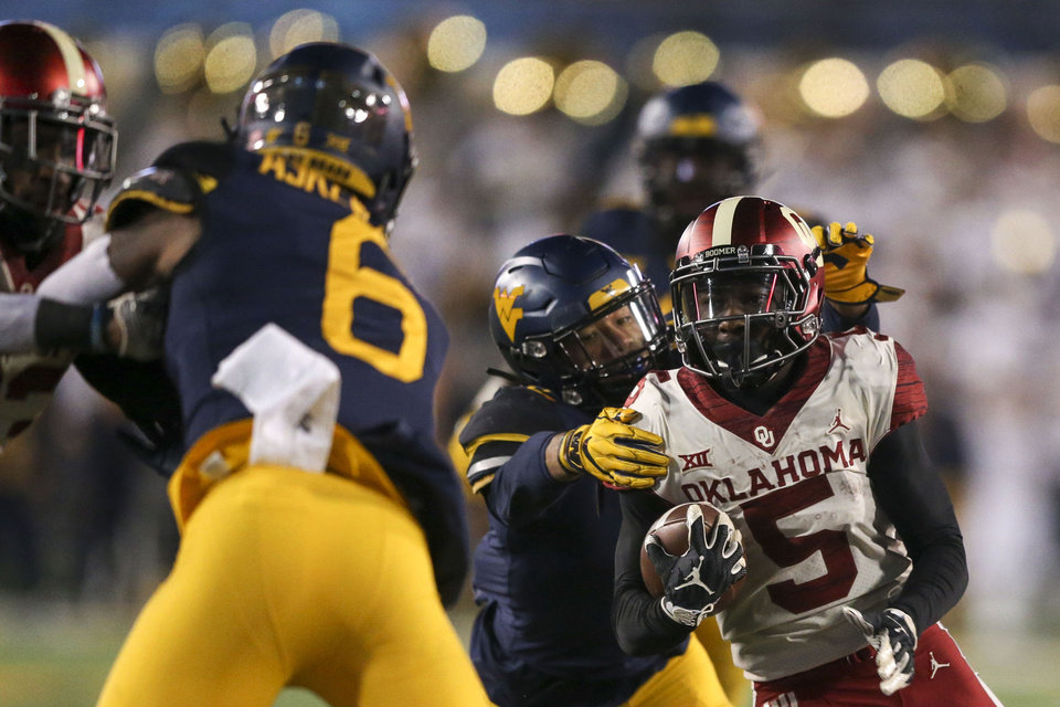 Photo - Oklahoma Sooners wide receiver Marquise Brown (5) gets tackled by West Virginia Mountaineers safety Kenny Robinson Jr. (2) during the NCAA football game between the Oklahoma Sooners and the West Virginia Mountaineers at Mountaineer Field at Milan Puskar Stadium in Morgantown, W.Va on Friday, November 23, 2018. IAN MAULE/Tulsa World