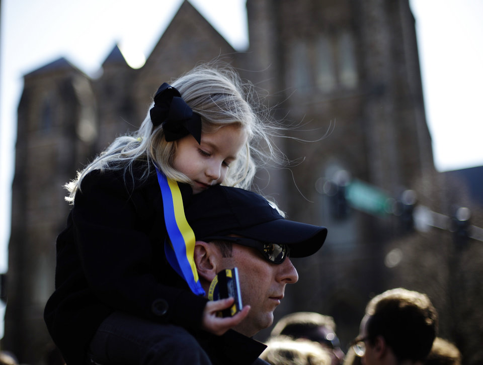 Marathon runner Nathan Finney of Boston and his daughter Mckenna, 5, gather with others ahead of an interfaith service with President Barack Obama at Cathedral of the Holy Cross, held in the wake of Monday\'s Boston Marathon explosions, which killed at least three and injured more than 140, Thursday, April 18, 2013, in Boston. (AP Photo/Matt Rourke)