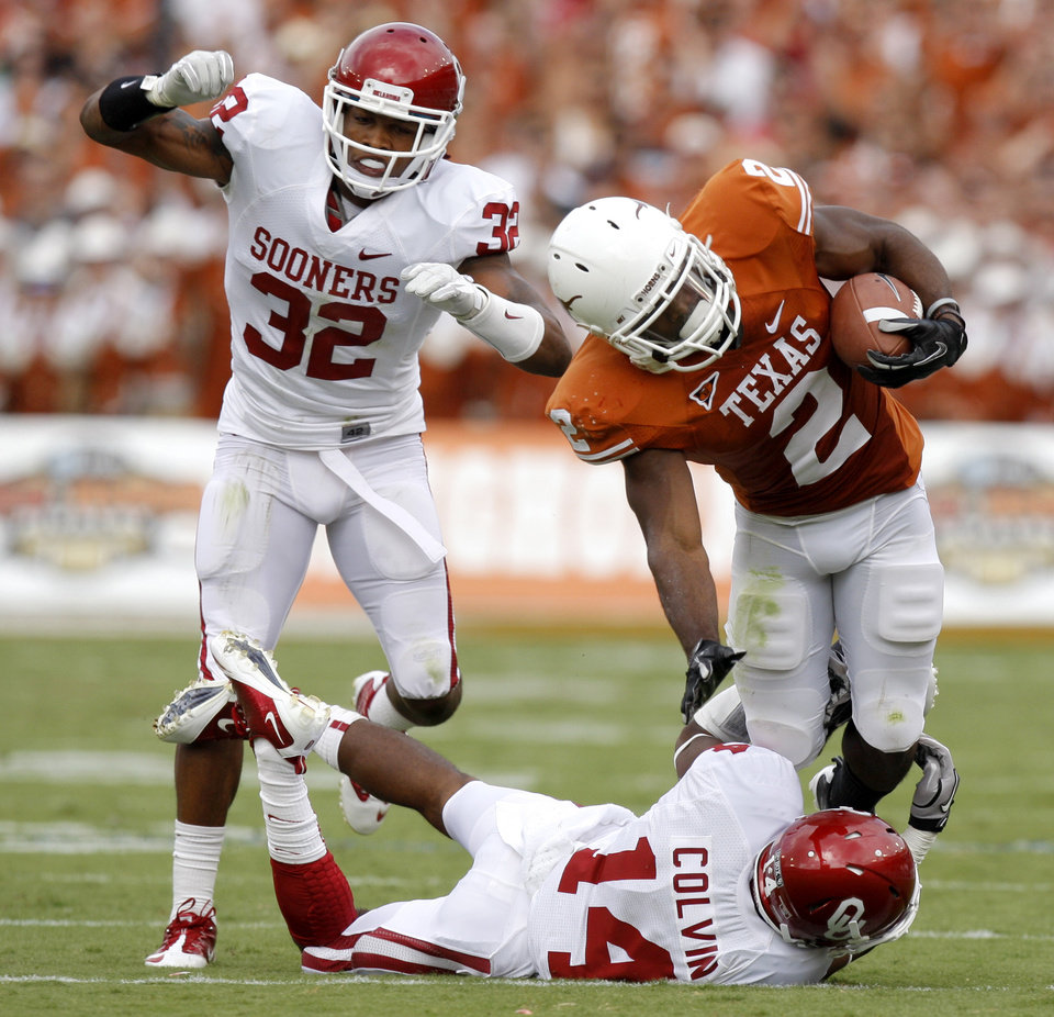 Photo - Texas' Fozzy Whittaker (2) is brought down by Oklahoma's Aaron Colvin (14) as Jamell Fleming (32) watches during the Red River Rivalry college football game between the University of Oklahoma Sooners (OU) and the University of Texas Longhorns (UT) at the Cotton Bowl in Dallas, Saturday, Oct. 8, 2011. Oklahoma won 55-17 Photo by Bryan Terry, The Oklahoman