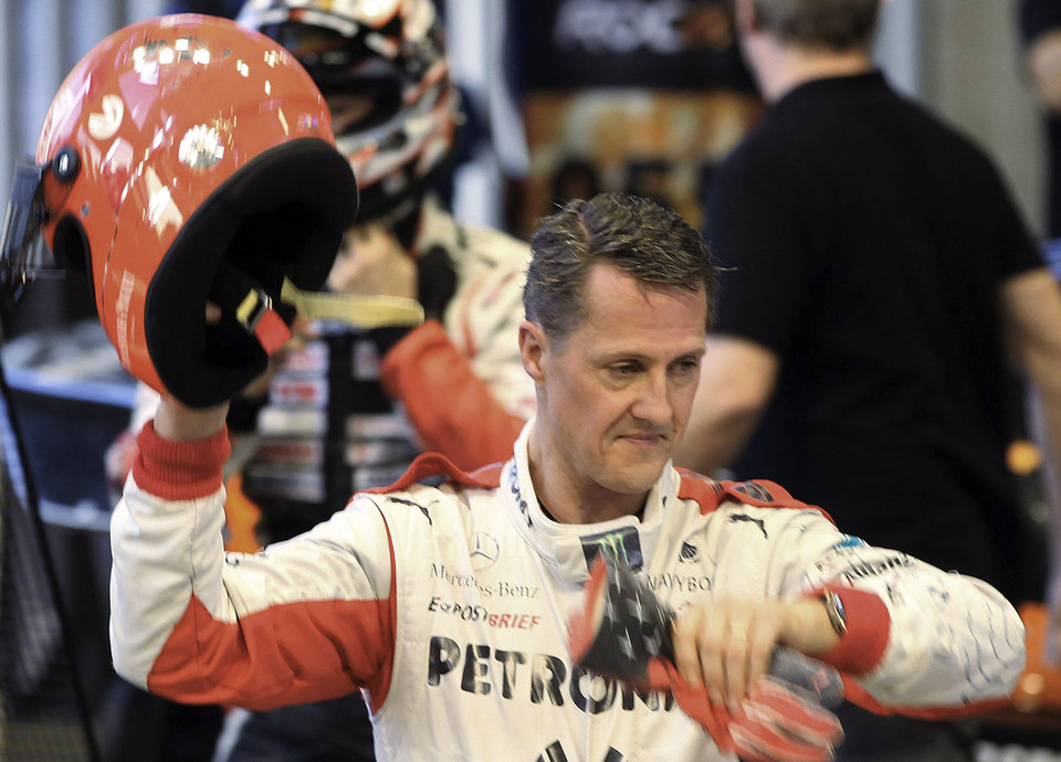 Photo - FILE - This is a Sunday, Dec. 16, 2012. file photo of  Michael Schumacher of Germany as he holds a helmet after a test drive prior to the Race Of Champions at Rajamangala national stadium in Bangkok, Thailand.  Schumacher's manager says the Formula One great is no longer in a coma and has left a French hospital where he had been receiving treatment since a skiing accident in December. Manager Sabine Kehm says in a statement Monday, June 16, 2014, that Schumacher has left the hospital in Grenoble