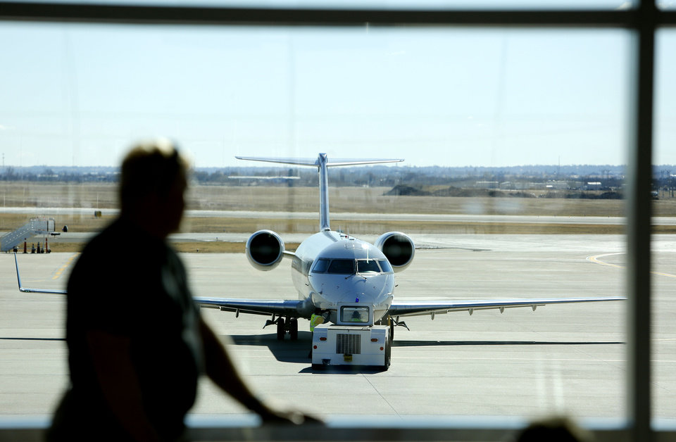 Photo - A passenger waits for his flight Tuesday, Nov. 26, 2013, at Will Rogers World Airport in Oklahoma City. Photo By Steve Gooch, The Oklahoman  Steve Gooch - The Oklahoman