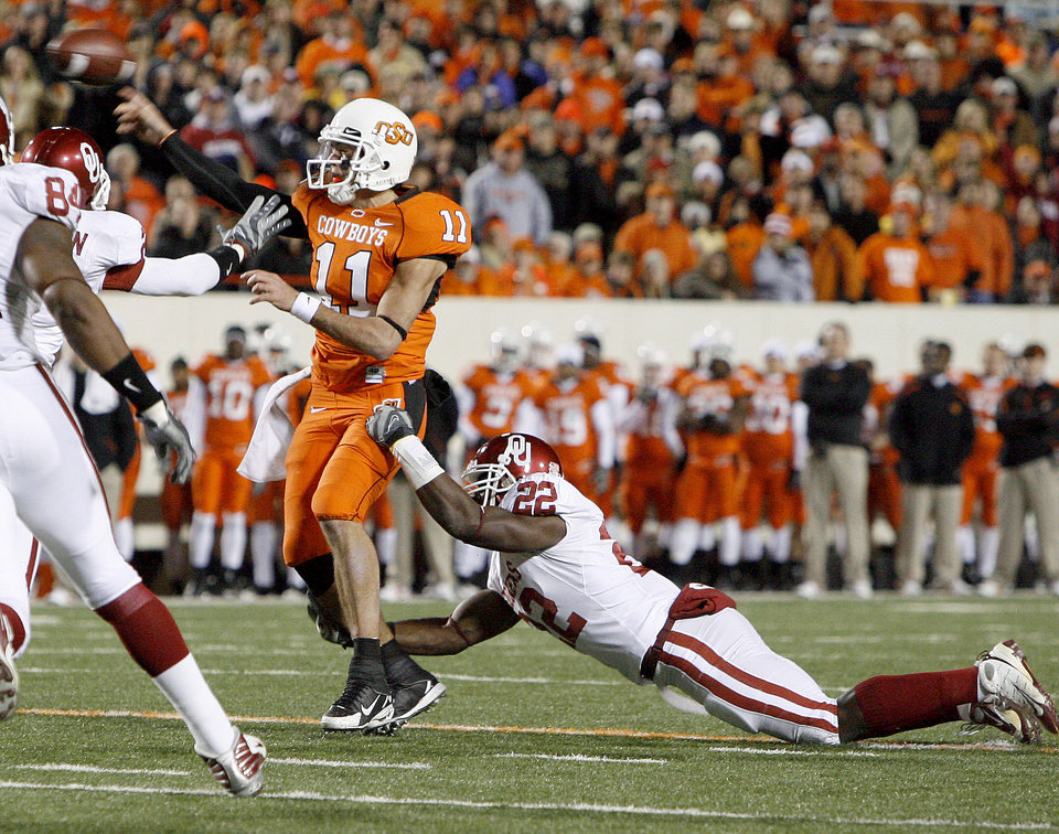 OSU's Zac Robinson throws a touchdown pass as OU's Keenan Clayton tries to tackle him during the college football game between the University of Oklahoma Sooners (OU) and Oklahoma State University Cowboys (OSU) at Boone Pickens Stadium on Saturday, Nov. 29, 2008, in Stillwater, Okla. STAFF PHOTO BY BRYAN TERRY