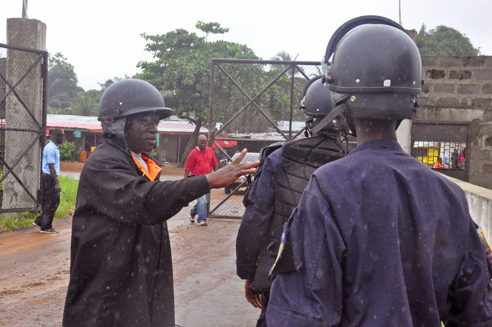 Photo - As it rains Liberian police deploy at an Ebola treatment center, to provide security in the city of Monrovia, Liberia, Monday, Aug. 18, 2014.  Liberia's armed forces were given orders to shoot people trying to illegally cross the border from neighboring Sierra Leone, which was closed to stem the spread of Ebola, local newspaper Daily Observer reported Monday. (AP Photo/Abbas Dulleh)