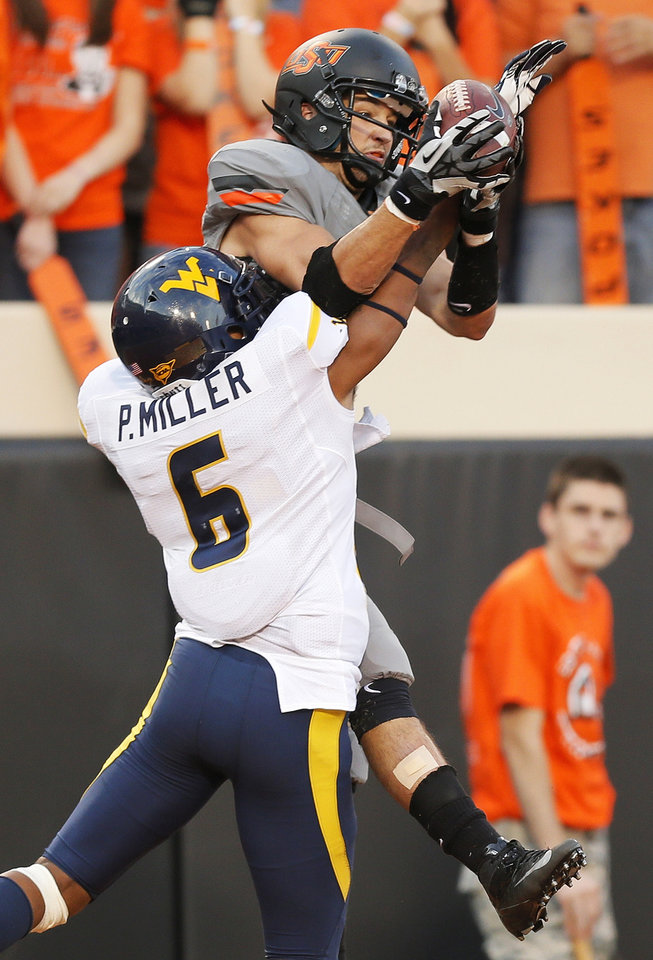 Photo - Oklahoma State's Charlie Moore (17) catches a touchdown pass against West Virginia's Pat Miller (6) in the third quarter during a college football game between Oklahoma State University (OSU) and West Virginia University (WVU) at Boone Pickens Stadium in Stillwater, Okla., Saturday, Nov. 10, 2012. OSU won, 55-34. Photo by Nate Billings, The Oklahoman