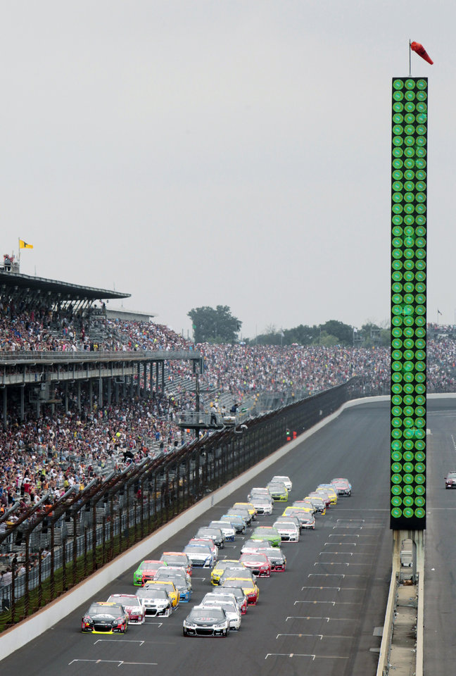 Photo - The field takes the green flag for the start of the NASCAR Brickyard 400 auto race at Indianapolis Motor Speedway in Indianapolis, Sunday, July 27, 2014. (AP Photo/AJ Mast)
