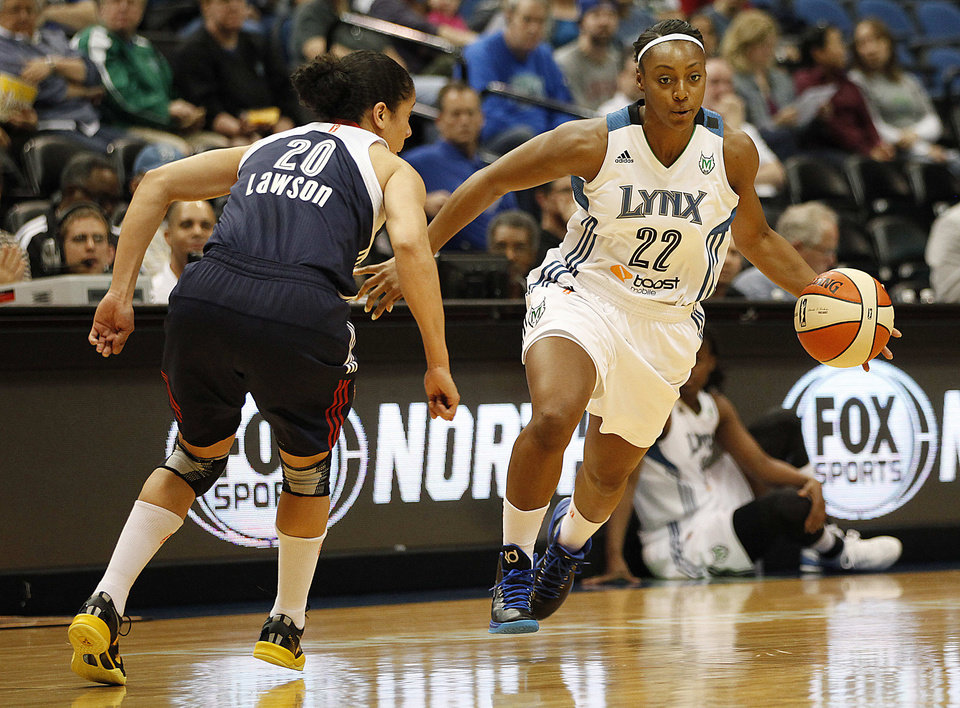 Photo - Minnesota Lynx guard Monica Wright (22) pushes the ball past Connecticut Sun guard Kara Lawson (20) in a WNBA preseason basketball game, Tuesday, May 21, 2013, in Minneapolis. (AP Photo/Stacy Bengs)