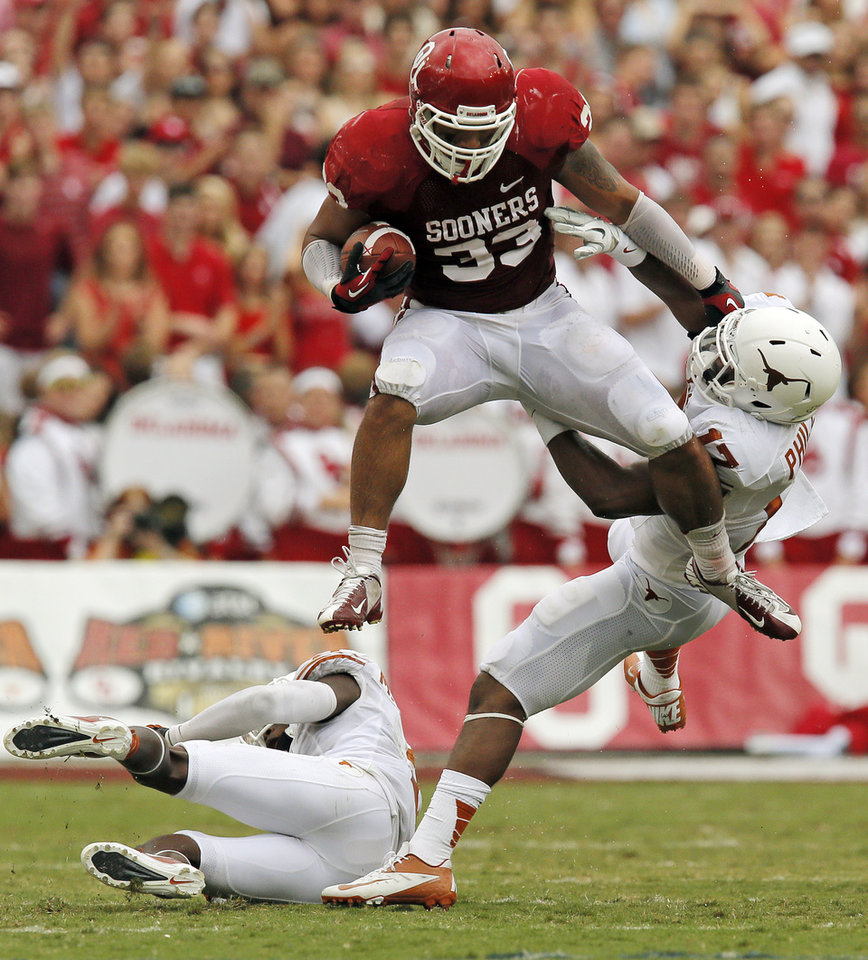 JUMP: OU's Trey Millard (33) leaps over UT's Mykkele Thompson (2) and pushes away Adrian Phillips (17) in the second quarter during the Red River Rivalry college football game between the University of Oklahoma (OU) and the University of Texas (UT) at the Cotton Bowl in Dallas, Saturday, Oct. 13, 2012. OU won, 63-21. Photo by Nate Billings, The Oklahoman