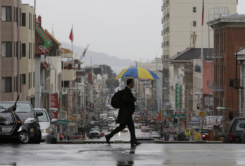Photo - A man crosses Stockton Street in San Francisco, Wednesday, Feb. 26, 2014. The first storm was expected to hit Northern California Wednesday morning and move down the coast, dumping a half-inch to an inch in southern areas late in the day, forecasters said. (AP Photo/Jeff Chiu)