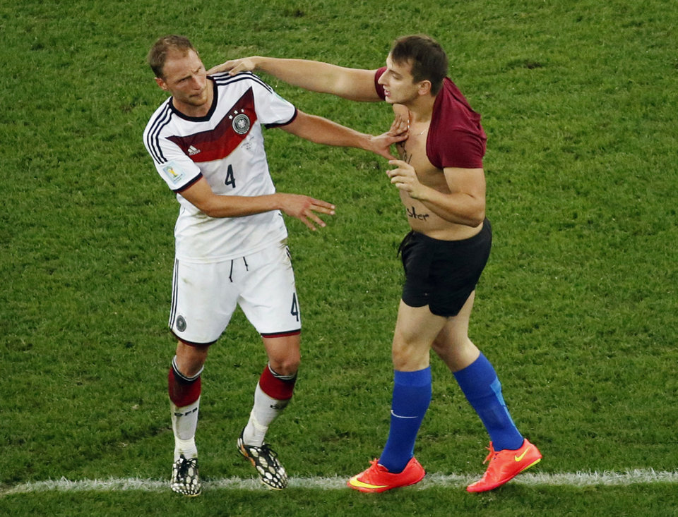 Photo - Germany's Benedikt Hoewedes faces a man who run into the pitch during the World Cup final soccer match between Germany and Argentina at the Maracana Stadium in Rio de Janeiro, Brazil, Sunday, July 13, 2014. (AP Photo/Fabrizio Bensch, Pool)