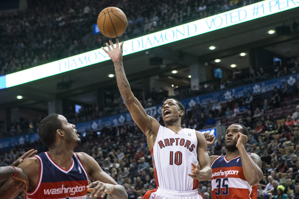 Photo - Toronto Raptors' DeMar DeRozan, center, shoots on Washington Wizards' Trevor Ariza, left, and Trevor Booker during first half NBA basketball action in Toronto, Thursday, Feb. 27, 2014. (AP Photo/The Canadian Press, Chris Young)
