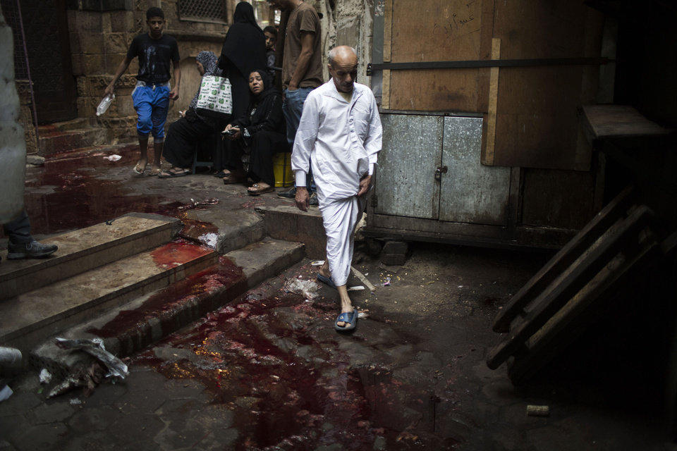 Photo - A man walks through an alley covered with bloodstained water on the first day of Eid al-Adha in Cairo, Egypt, Tuesday, Oct. 15, 2013. Muslims worldwide are celebrating Eid al-Adha, or the Feast of the Sacrifice, by sacrificial killing of sheep, goats, cows or camels. The slaughter commemorates the biblical story of Abraham, who was on the verge of sacrificing his son to obey God's command, when God interceded by substituting a ram in the child's place. (AP Photo/Manu Brabo)
