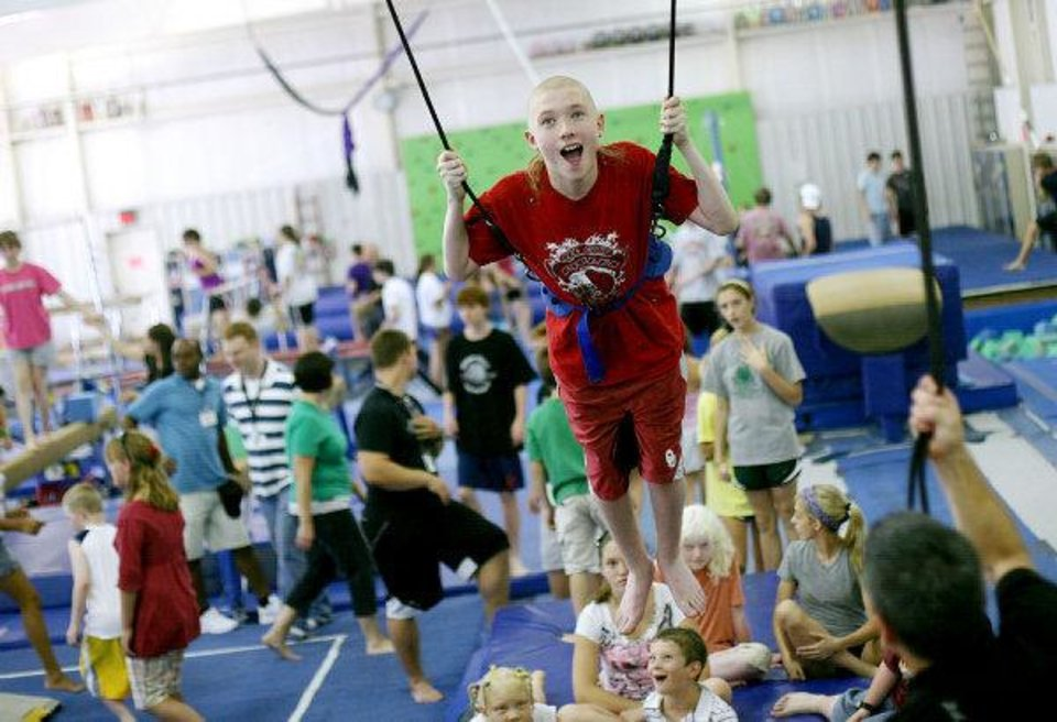 Kane Burton, 16, of Oklahoma City, who is visually impaired, soars in a harness at Mat Trotters Gymnastics in Oklahoma City on Wednesday. PHOTO BY JOHN CLANTON, THE OKLAHOMAN <strong>JOHN CLANTON - John Clanton</strong>