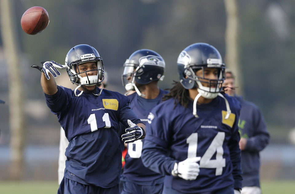 Photo - Seattle Seahawks wide receiver Percy Harvin (11) tosses a ball back as players ready for NFL football practice, Friday, Jan. 3, 2014, in Renton, Wash. Seattle plays at home in a playoff game on Jan. 11.  (AP Photo/Ted S. Warren)