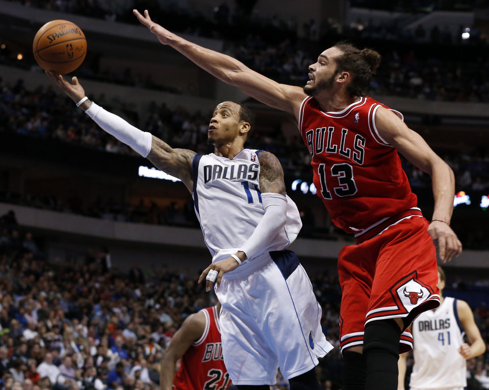 Photo - Chicago Bulls center Joakim Noah (13) reaches out to try to block a shot by Dallas Mavericks guard Monta Ellis (11) during the first half of an NBA basketball game on Friday, Feb. 28, 2014, in Dallas. (AP Photo/John F. Rhodes)
