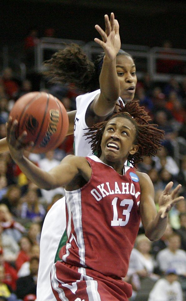 Photo - OU's Danielle Robinson shoots the ball from under Notre Dame's Devereaux Peters during the Sweet 16 round of the NCAA women's  basketball tournament in Kansas City, Mo., on Sunday, March 28, 2010. 