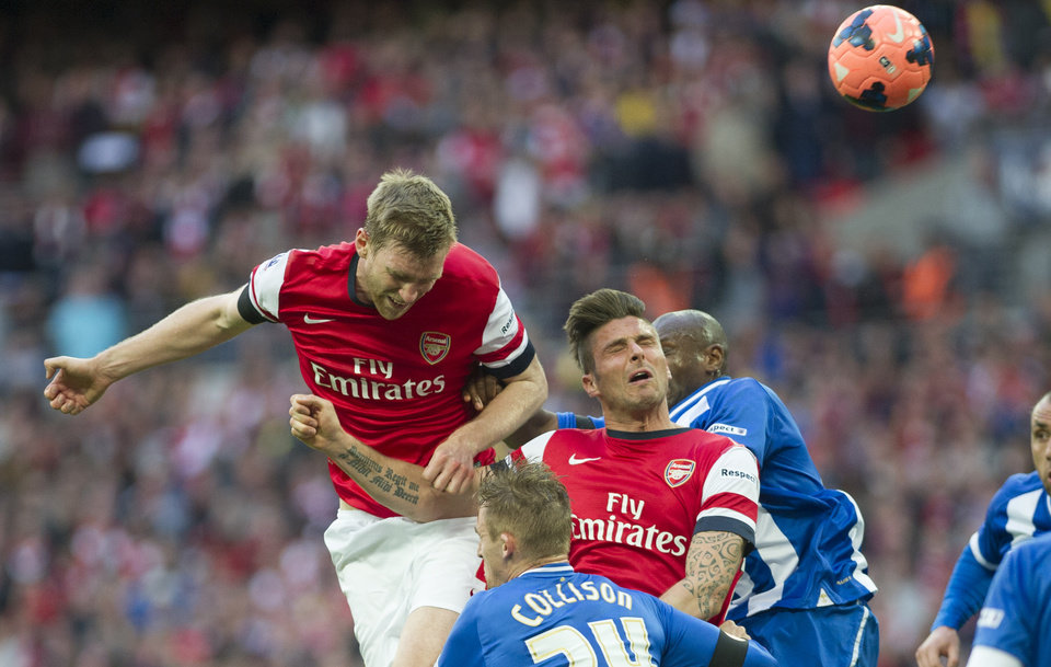 Photo - Arsenal's Per Mertesacker, left, tries to score against Wigan Athletic during their English FA Cup semifinal soccer match, at the Wembley Stadium in London, Saturday, April 12, 2014. (AP Photo/Bogdan Maran)