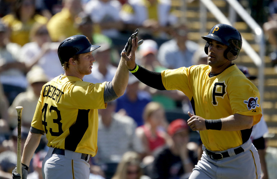 Photo - Pittsburgh Pirates' Andrew Lambo, right, high-fives teammate Jared Goedert after scoring off a single by Jeff Larish in the seventh inning of a spring training exhibition baseball game against the Minnesota Twins, Sunday, March 10, 2013, in Fort Myers, Fla. Pittsburgh won 7-4. (AP Photo/David Goldman)