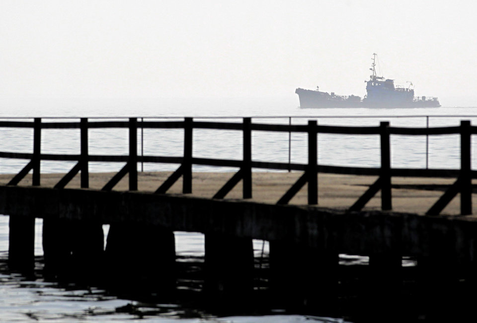 Photo - A ship sails by the port of Kerch, Ukraine, Monday, March 3, 2014. Pro-Russian troops controlled a ferry terminal on the easternmost tip of Ukraine's Crimea region close to Russia on Monday, intensifying fears that Moscow will send even more troops into the strategic Black Sea region in its tense dispute with its Slavic neighbor. (AP Photo/Darko Vojinovic)