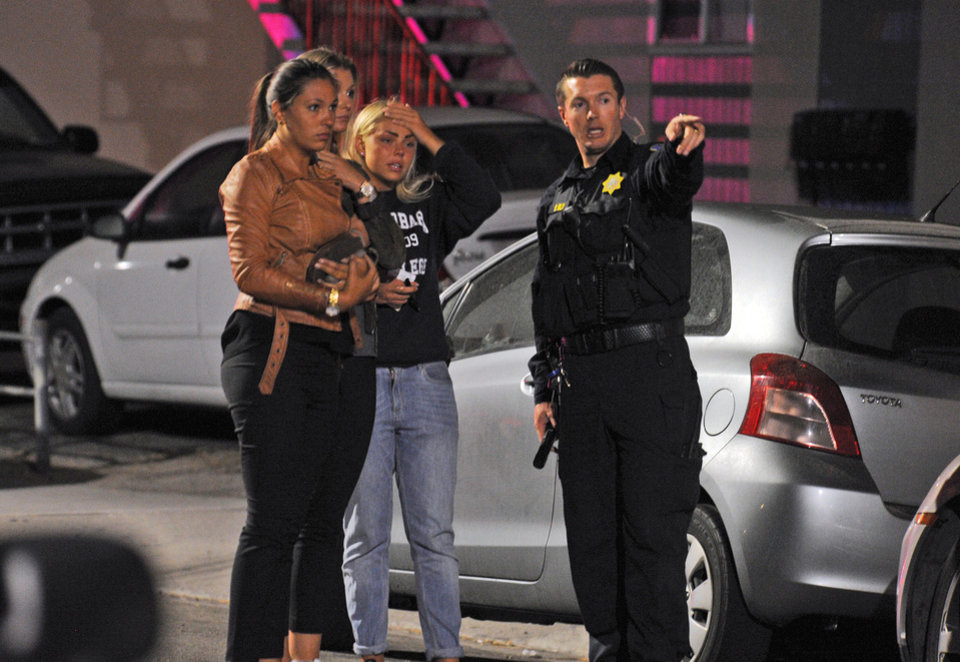 Photo - In this image provided by the Santa Barbara Independent, people speak to a police officer after a mass shooting near the campus of the University of Santa Barbara in Isla Vista, Calif., Friday, May 23, 2014. A drive-by shooter went on a rampage near the Santa Barbara university campus that left seven people dead, including the attacker, and others wounded, authorities said Saturday. (AP Photo/Santa Barbara Independent, Paul Wellman) MANDATORY CREDIT