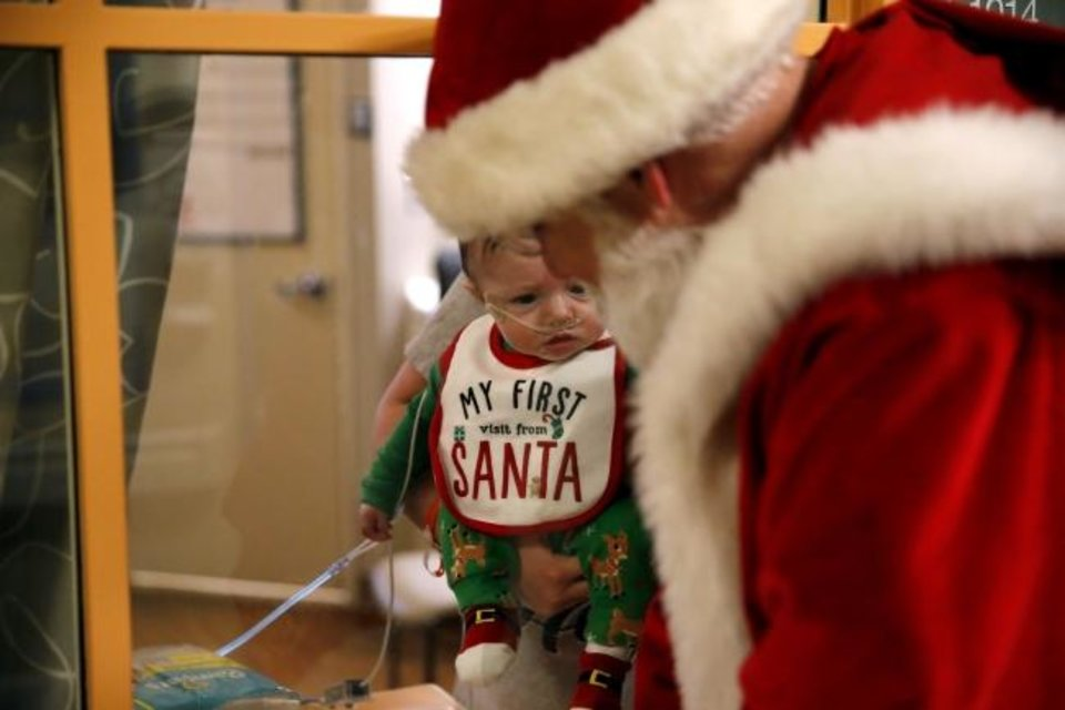 Photo -  Santa Claus talks to Briggs Cole, 4 months, through a window at Integris Children´s at Baptist Medical Center. Cole was in isolation on Christmas Eve.  [Sarah Phipps/The Oklahoman]