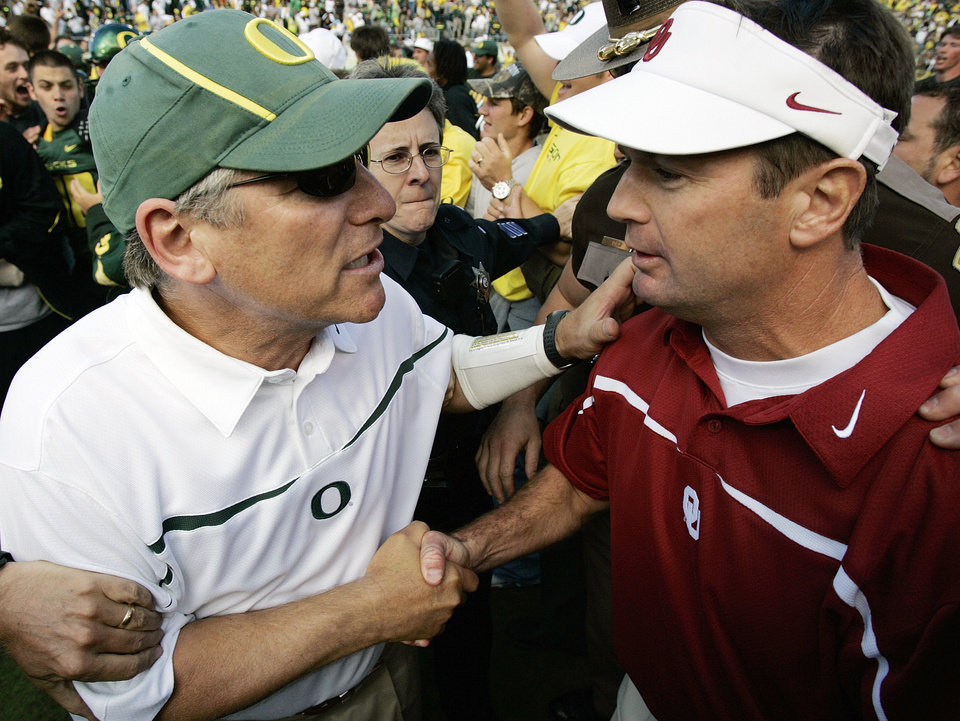 Photo - Oregon head coach Mike Bellotti, left, talks to Oklahoma head coach Bob Stoops after the University of Oklahoma Sooners (OU) college football game against University of Oregon Ducks (UO) at Autzen Stadium, on Saturday, Sept. 16, 2006, in Eugene, Ore. Oregon won, 34-33. By Nate Billings, The Oklahoman  ORG XMIT: KOD