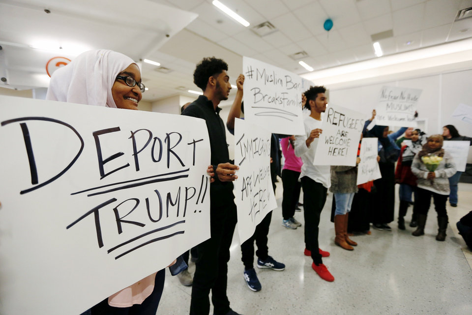 Photo - Protestors demonstrate against President Trump's executive order banning Muslims from certain middle eastern countries from entering the United States at Dallas Forth Worth Airport, Saturday, Jan. 28, 2017, in Dallas. (Brandon Wade/Star-Telegram via AP)