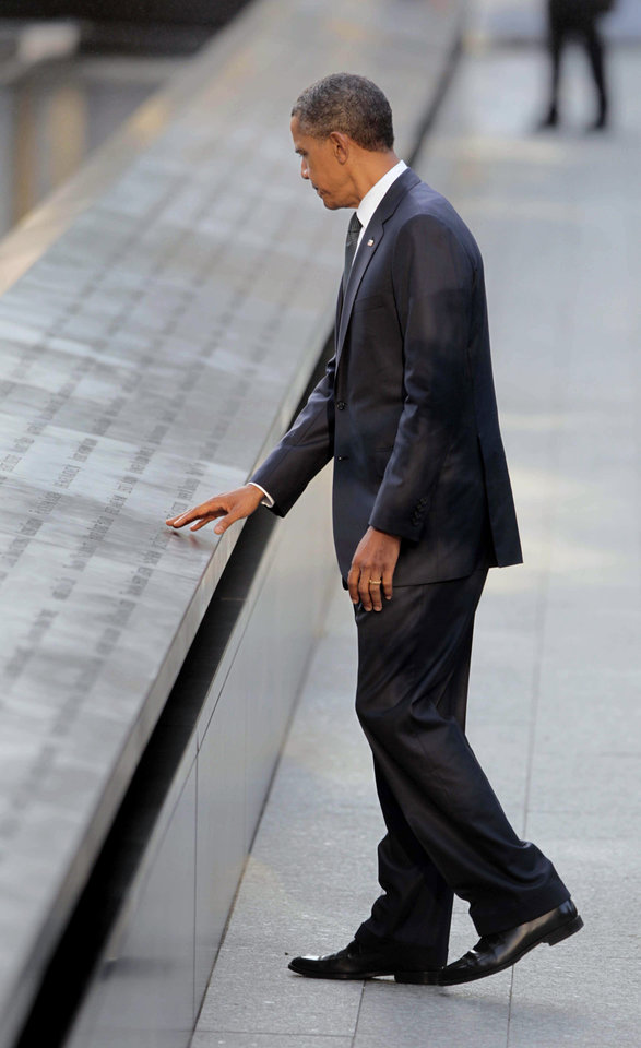 Photo -   President Barack Obama touches names of the 9/11 victims as he visits the North Memorial Pond at the National Sept. 11th Memorial ceremony Sunday, Sept., 11, 2011 in New York. (AP Photo/Pablo Martinez Monsivais)