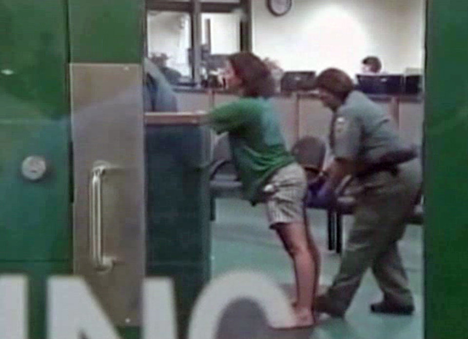 This framegrabbed image provided by Baynews9 shows Sharyn Hakken being processed for booking into the Hillsbourgh County Jail early Wednesday morning April 10, 2013. The Florida couple accused of kidnapping their two young sons and fleeing by boat to Havana were handed over to the United States, and were booked into a Florida jail, officials said Wednesday. (AP Photo/Baynews9, Pool)