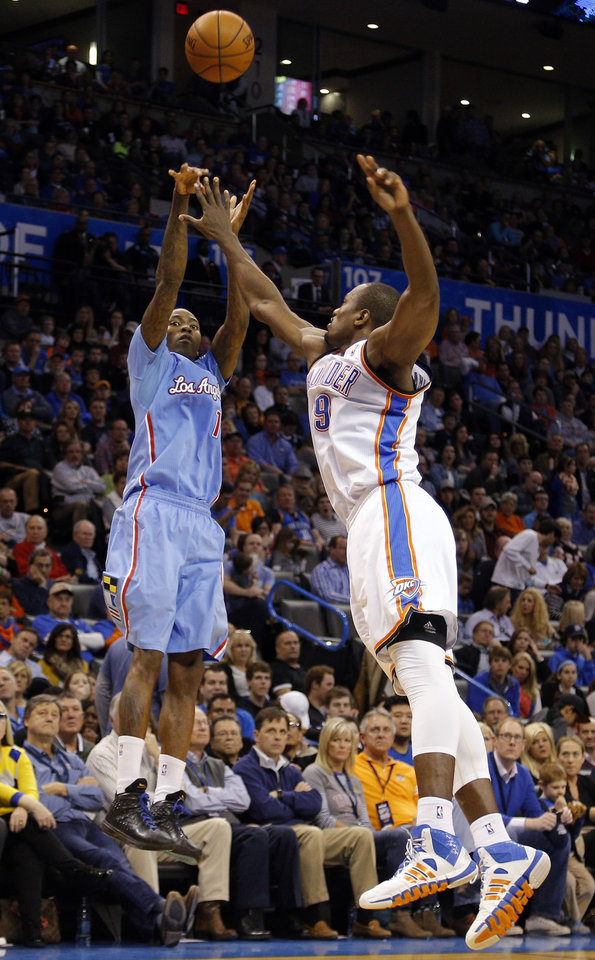 Photo - Oklahoma City 's Serge Ibaka (9) defends against Jamal Crawford (11) during the NBA game between the Oklahoma City Thunder and the Los  Angeles Clippers at the Chesapeake Energy Arena, Sunday, Feb. 23, 2014. Photo by Sarah Phipps, The Oklahoman