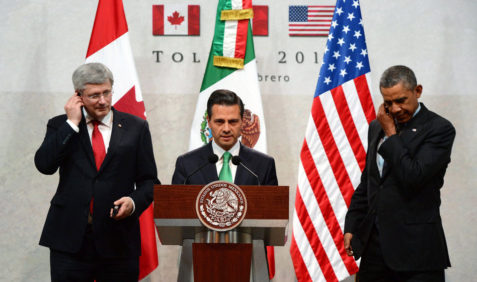 Photo - Canada's Prime Minister Stephen Harper, left, and President Barack Obama, right, look on as Mexico's President Enrique Pena Nieto speaks at a news conference during the North American Leaders Summit in Toluca, Mexico, Wednesday, Feb. 19, 2014. Obama is in Toluca for a one-day summit with Mexican and Canadian leaders, meeting on issues of trade and other neighbor-to-neighbor interests, even as Congress is pushing back against some of his top cross-border agenda items. (AP Photo/The Canadian Press, Sean Kilpatrick )