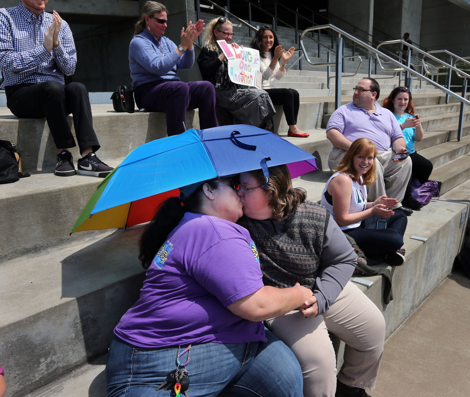 Photo - Stephanie Steele, left, and Amy Stinnett, of Eugene, embrace under a rainbow umbrella with other supporters of same sex marriage Monday, May 19, 2014, on the steps of the Wayne Morse Federal Courthouse in Eugene, Ore, after the news that marriage between people of the same sex is now legal in Oregon. (AP Photo/The Register-Guard, Chris Pietsch)