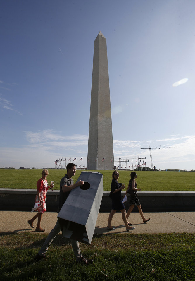 Photo - Steven Avila, an Interior Department employee, carries a Washington Monument costume as he arrives at the Washington Monument in Washington, Monday, May 12, 2014, ahead of a ceremony to celebrate its re-opening. The monument, which sustained damage from an earthquake in August 2011, is reopening to the public today. Avila made the costume to show his support for the re-opening of the monument. (AP Photo)