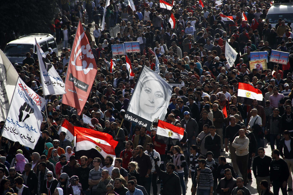 Egyptian demonstrators march from Moustafa Mahmoud mosque towards Tahrir Square in Cairo, Egypt, Friday, Jan. 25, 2013. Two years after Egypt's revolution began, the country's schism was on display Friday as the mainly liberal and secular opposition held rallies saying the goals of the pro-democracy uprising have not been met and denouncing Islamist President Mohammed Morsi. Banner in center shows an image of Egyptian feminist, Hoda Shaarawi who called for Egyptian women to remove the veil in 1922. (AP Photo/Ahmed Abd el Fattah) ORG XMIT: CAI106