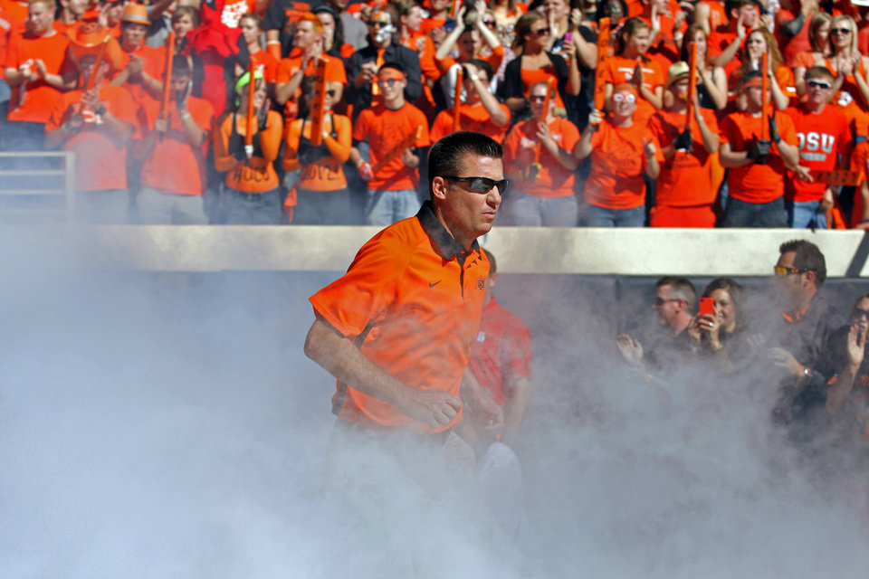 Photo - Oklahoma State head coach Mike Gundy runs on to the field before a college football game between Oklahoma State University (OSU) and Iowa State University (ISU) at Boone Pickens Stadium in Stillwater, Okla., Saturday, Oct. 20, 2012. Photo by Sarah Phipps, The Oklahoman
