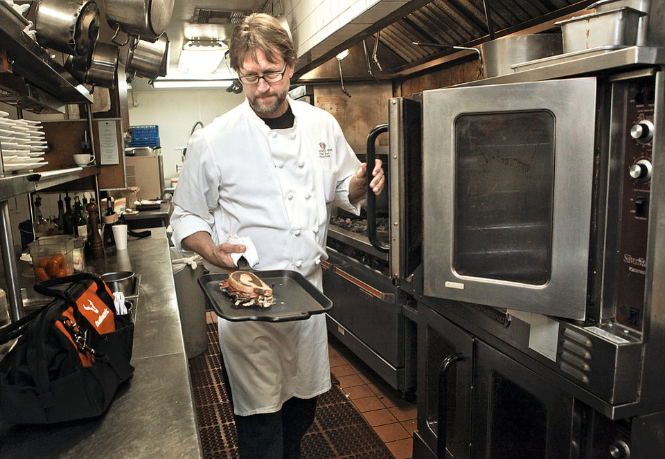 The Coach House chef Kurt Fleischfresser puts one of the the restaurant's corned beef sandwiches in an oven. PHOTO BY CHRIS LANDSBERGER, THE OKLAHOMAN