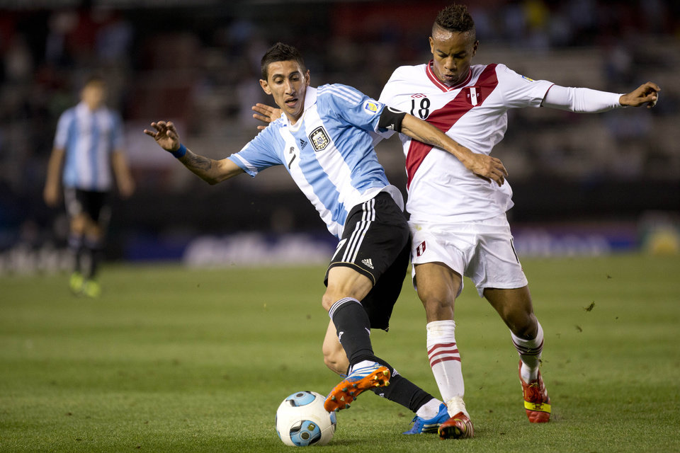 Photo - FILE - In this Oct. 11, 2013, file photo, Argentina's Angel Di Maria, left, vies for the ball with Peru's Andre Carrillo during a 2014 World Cup qualifying soccer match in Buenos Aires, Argentina. (AP Photo/Eduardo Di Baia)