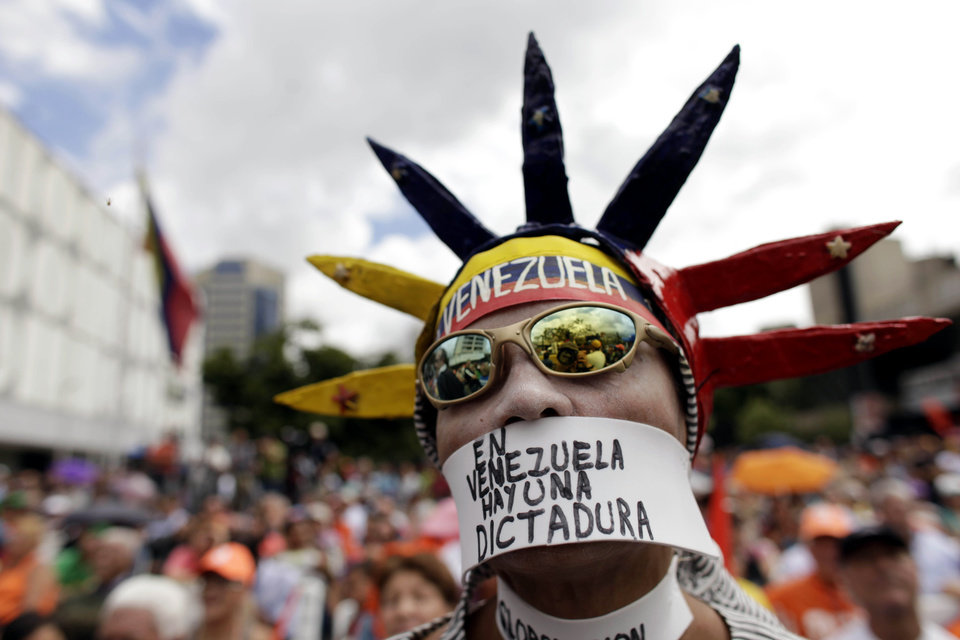 "An opponent of Venezuela's President Hugo Chavez wears a message over his mouth that reads in Spanish, ""In Venezuela there is a dictatorship,"" during an outdoor gathering in Caracas, Venezuela, Saturday, Jan. 12, 2013. Venezuelan opposition politicians say they're preparing to present a case before a regional human rights court to challenge a Supreme Court decision that permits the indefinite postponement of President Hugo Chavez's inauguration. (AP Photo/Ariana Cubillos)"