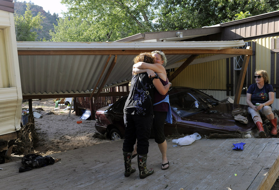 Photo - Molly Morton, left, hugs Jenna Brink, center right, outside Brink's flood-damaged trailer at the River Bend Mobile Home Park in Lyons, Colo., as Brink's mother, Christine Brink takes a break from clearing belongings from the trailer on Thursday, Sept. 19, 2013. Hundreds of evacuees were allowed past National Guard roadblocks Thursday to find a scene of tangled power lines, downed utility poles, and mud-caked homes and vehicles. (AP Photo/Chris Schneider)