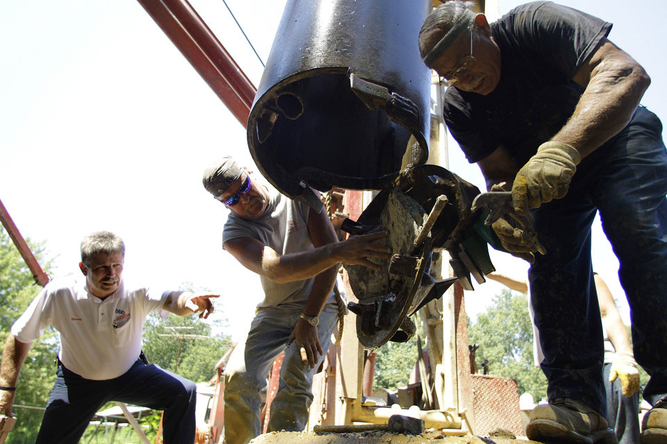 Photo - Randy Gebke of Kohnen Concrete Products, left, helps out with a water well drilling crew on a site which he witched for water in Huey, Ill. AP Photo  Seth Perlman