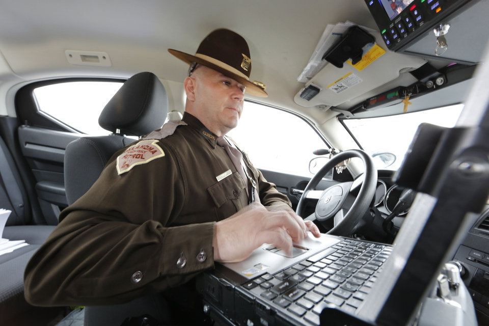 Photo -  Oklahoma Highway Patrol trooper Mike Moler uses his computer after he stopped a motorist for speeding Jan. 25 on Interstate 240 in Oklahoma City. Photo By Steve Gooch, The Oklahoman  Steve Gooch