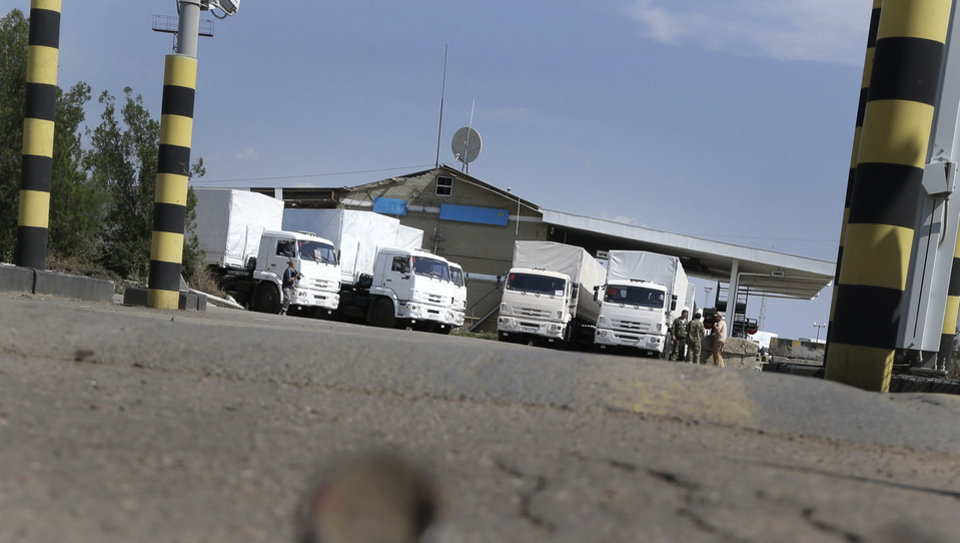 Photo - The first trucks of convoy park prior to passing the border post at Izvaryne, eastern Ukraine, Friday, Aug. 22, 2014. The first trucks in a Russian aid convoy crossed into eastern Ukraine on Friday, seemingly without Kiev's approval, after more than a week's delay amid suspicions the mission was being used as a cover for an invasion by Moscow. (AP Photo/Sergei Grits)
