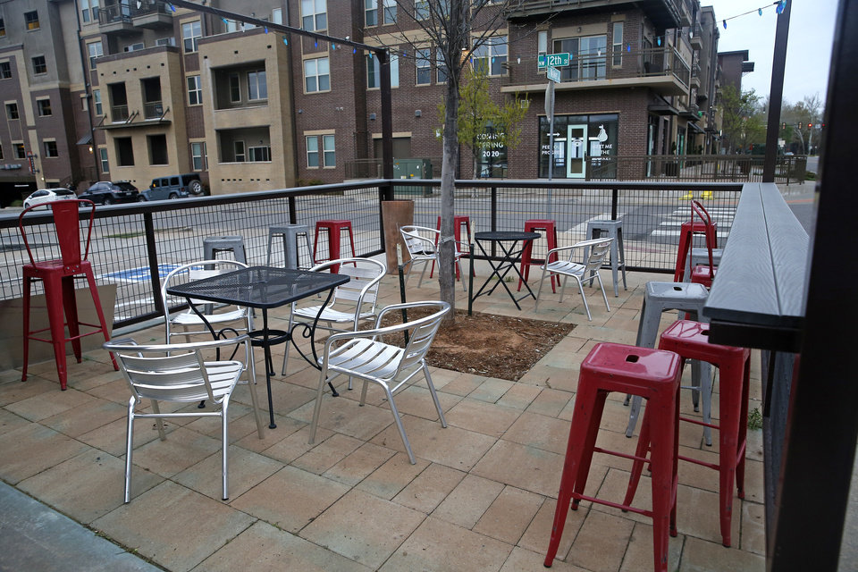 Photo - Empty chairs are pictured at Not Your Average Joe  in Midtown in Oklahoma City,  Okla.,  Friday, March 27, 2020.  [Sarah Phipps/The Oklahoman]