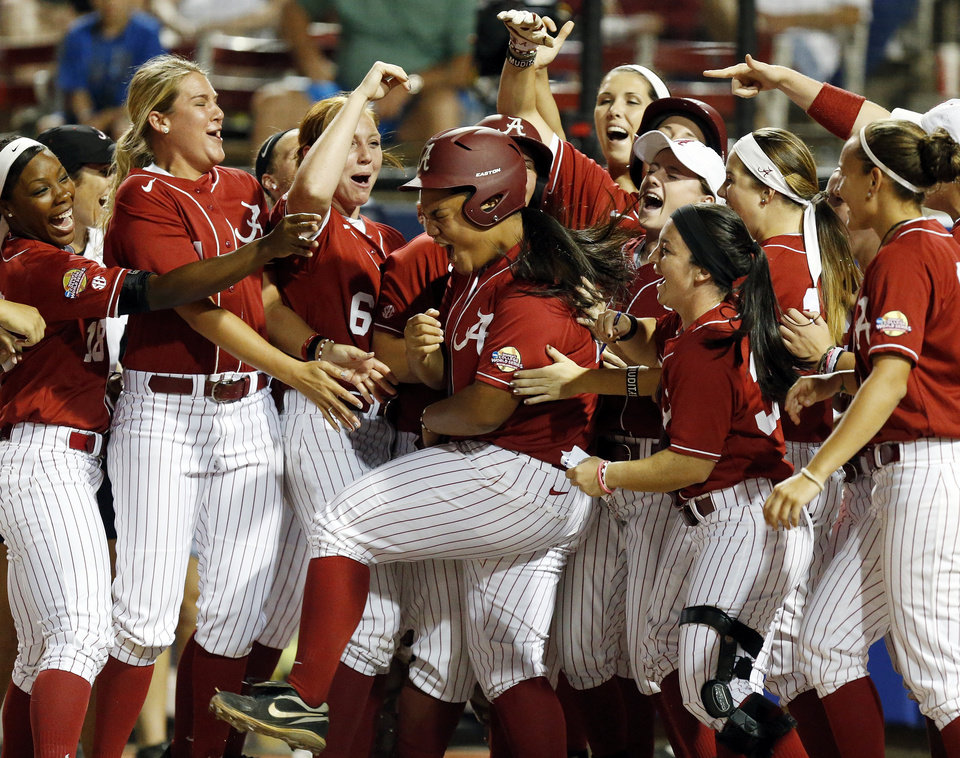 Photo - Alabama celebrates a 2-run home run by Leona Lafaele (24) in the 2nd inning  during Game 6 of the Women's College World Series softball tournament between Alabama and Kentucky at ASA Hall of Fame Stadium in Oklahoma City, Friday, May 30, 2014. Alabama won, 2-0. Photo by Nate Billings, The Oklahoman