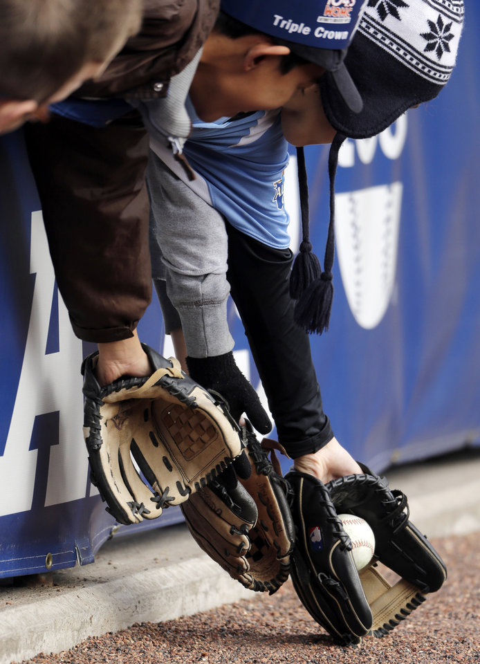 Photo -   Fans field a foul ball during batting practice before Game 4 of the American League championship series between the Detroit Tigers and New York Yankees Thursday, Oct. 18, 2012, in Detroit. (AP Photo/Charlie Riedel)