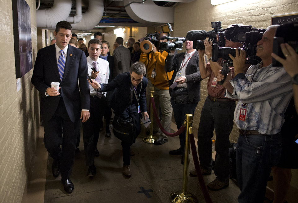 Photo - House Budget Committee chairman Rep. Paul Ryan walks to a House GOP meeting on Capitol Hill on Tuesday, Oct. 15, 2013 in Washington. The federal government remains partially shut down and faces a first-ever default between Oct. 17 and the end of the month. (AP Photo/ Evan Vucci)