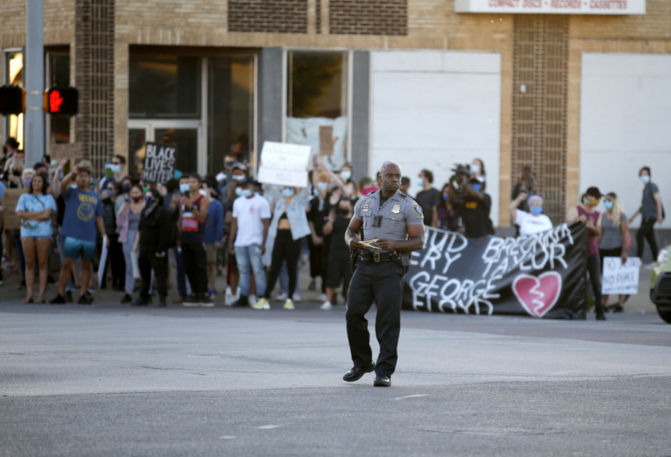 Photo - An Oklahoma City Police Officer clears the intersection of 23rd and Classen in Oklahoma City, Saturday, May 30, 2020. The protest was in response to the death of George Floyd. [Sarah Phipps/The Oklahoman]