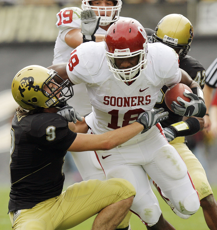 Photo - Oklahoma's Jermaine Gresham (18) runs over Colorado's Daniel Dykes (9) as he takes the ball up field during the first half of the college football game between the University of Oklahoma Sooners (OU) and the University of Colorado Buffaloes (CU) at Folsom Field in Boulder, Co., on Saturday, Sept. 28, 2007. 