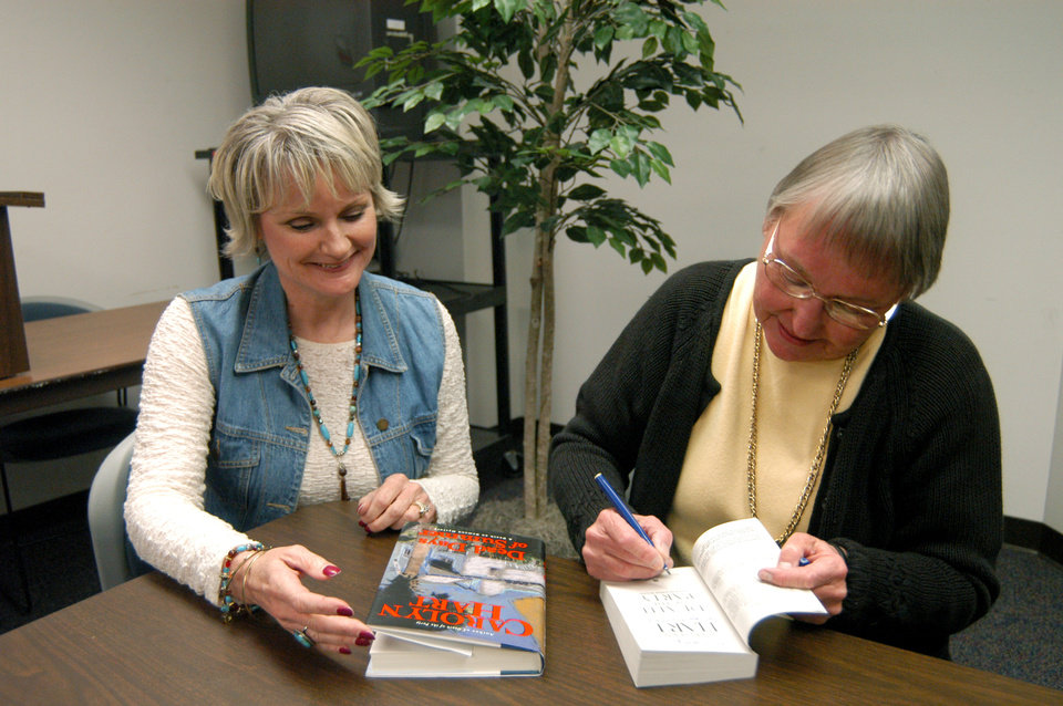 Mystery author, Carolny G.Hart, pictured right, signs book for Carolny Sims. The book signing was held recently at Rose State College<br/><b>Community Photo By:</b> Steve Reeves<br/><b>Submitted By:</b> natalie,